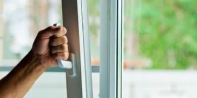 Человек открывает ПВХ окно